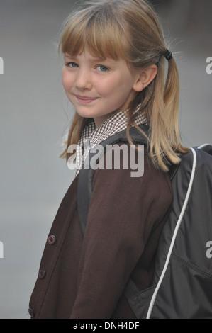 pretty schoolgirl in school uniform walks to school - Stock Photo