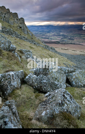 Lichen covered rocks on Clee Hill while the sun shines through the clouds creating Crepuscular rays in the background. - Stock Photo