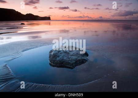 The retreating tide leaves a pool around a rock in the sand on the beach at Sandsend, North Yorkshire at sunset. - Stock Photo