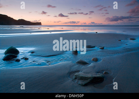 The retreating tide leaves a pool around a group of rocks in the sand on the beach at Sandsend, North Yorkshire - Stock Photo