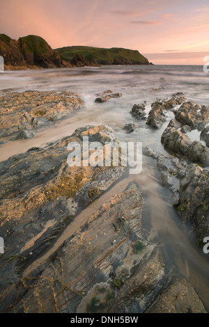 The tide rolls in over the rocks on the beach at Hope Cove, Devon. The sunrise casts a warm glow over the landscape - Stock Photo
