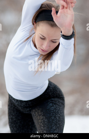 A beautiful young woman in tights stretches before a run on a cold, winter day. - Stock Photo