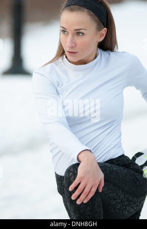 A beautiful woman stretches before a run on a cold winter day - Stock Photo