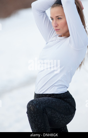 A beautiful woman stretches before a run on a cold winter day. - Stock Photo