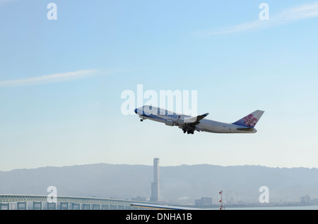 Old Jumbo Jet (Boeing 747) operating as a freighter, taking off from an airport - Stock Photo