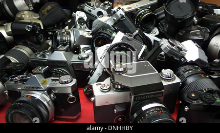A collection of second hand FILM cameras for sale in a photographic store window in Cardiff City Centre Wales UK - Stock Photo