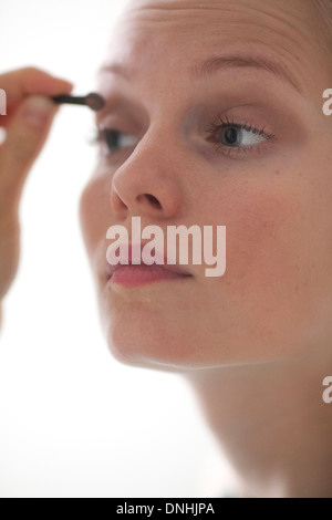 Woman Applying Make-up in Mirror - Stock Photo