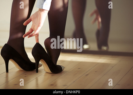 Closeup of a young woman legs wearing high heel shoes in front of mirror at home. Young female getting dressed indoors. - Stock Photo