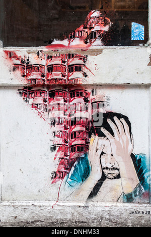 Jana and JS street art - Anguished man holding head in hands in Hanbury Street, off Brick lane, East London, UK - Stock Photo