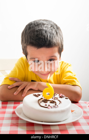 Six year old boy looks at birthday cake - Stock Photo