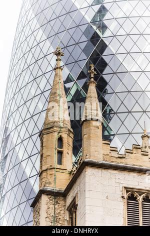 The Gherkin reflecting St Andrew Undershaft church, St Mary Axe and Leadenhall Street, City of London, UK - Stock Photo