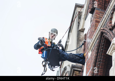Specialist jobs: Workman carrying tools abseiling down the exterior of a building in London in a safety harness - Stock Photo