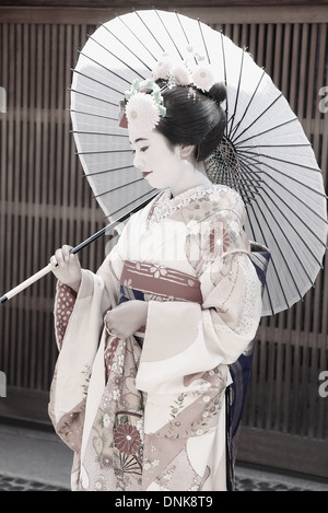KYOTO,JAPAN - OCTOBER 14: Maiko poses for a photographer with white umbrella on October 14, 2013 in kyoto. - Stock Photo