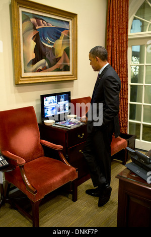US President Barack Obama watches news coverage of the passing of Nelson Mandela in the Outer Oval Office December - Stock Photo
