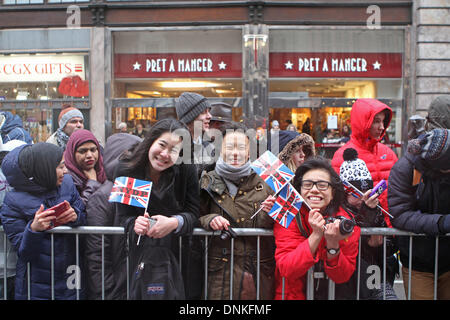 London,UK,1st January 2014,Crowds smile despite the rain waiting for the London's New Year's Day Parade 2014 Credit: - Stock Photo