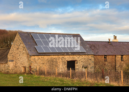 Solar panels on a roof of an old barn on a rural Welsh farm in Anglesey, North Wales, UK, Britain - Stock Photo