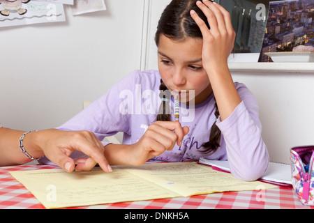 Parent helping schoolgirl with homework - Stock Photo