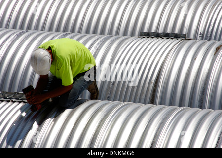 A construction man tightening bolts on a steel pipe for stormwater retention - Stock Photo