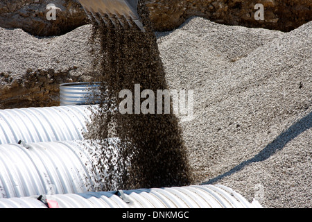 Gravel backfill being placed around stormwater storage metal cisterns used for water quality - Stock Photo