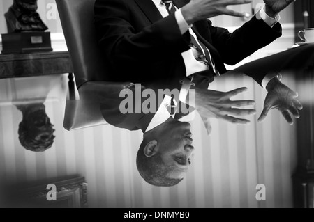 US President Barack Obama is reflected in a glass table top during a meeting in the Oval Office of the White House - Stock Photo