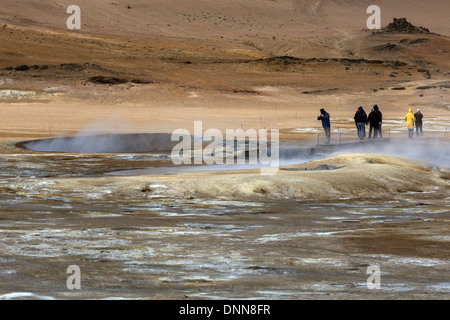 Tourists on the Hverarond geothermal hot spring area examining the steaming and bubbling mud pools, north east Iceland - Stock Photo