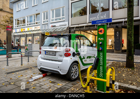 Smart electric drive electrically powered compact car charging the battery on an electric vehicle charging station, - Stock Photo