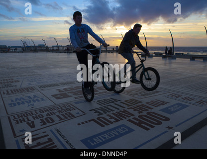 Teenage Boys performing bicycle tricks on the Blackpool Comedy Carpet or Pavement at sunset. Lancashire, UK - Stock Photo