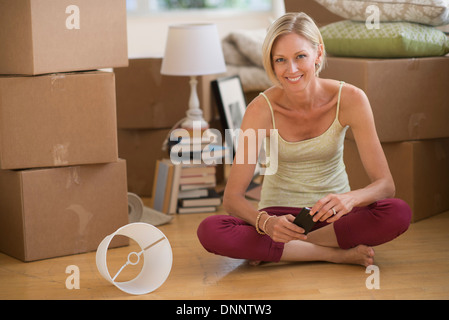 Portrait of woman sitting on floor of new home - Stock Photo