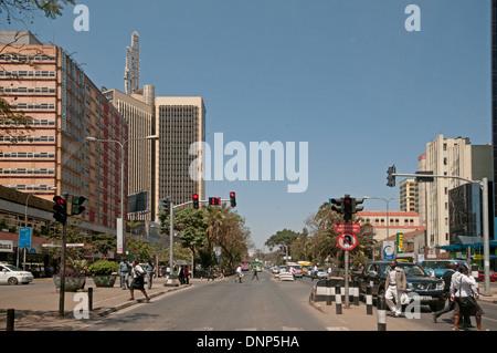 Traffic lights and pedestrians on Kenyatta Avenue Nairobi Kenya with Post Office Tower top left - Stock Photo