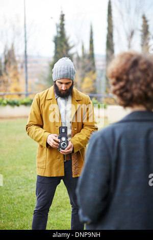Young bearded hipster taking photo to redhead girl with TLR camera outdoors - Stock Photo