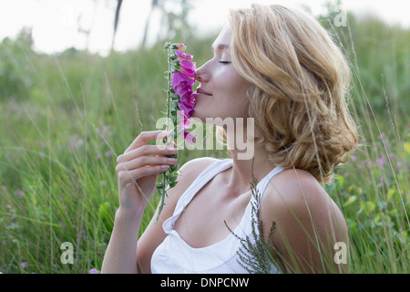Netherlands, Gelderland, Hatertse Vennen, Portrait of happy woman with purple flower - Stock Photo