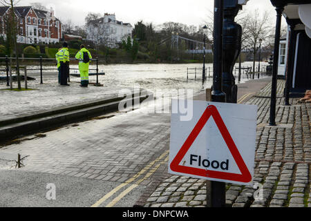 Police and Environment Agency workers monitor the high tide and flooding on the River Dee at The Groves in Chester - Stock Photo