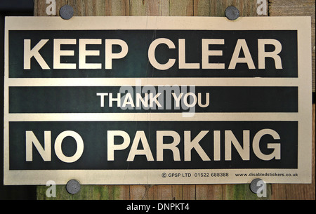 'Keep Clear, Thank You, No Parking' sign attached to a wooden pole with nails - Stock Photo