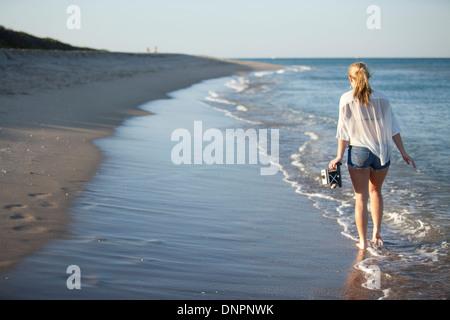 Young Woman Carrying Camera while Walking along Beach, Palm Beach Gardens, Palm Beach, Florida, USA - Stock Photo