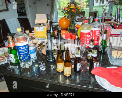 Messy, untidy kitchen after a party: empty wine, beer & drink glass bottles, plastic bottles, dirty paper plates, - Stock Photo