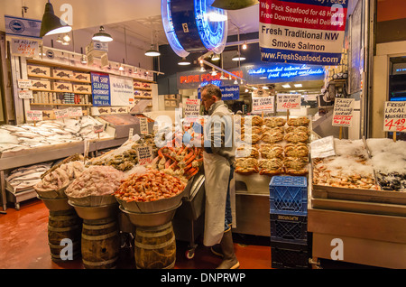 Fish monger arranging crab legs in a market stall Pike Place Market Seattle, Washington, USA - Stock Photo