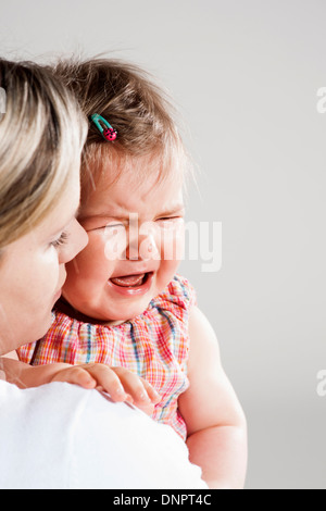 Portrait of Mother holding Crying Baby Girl, Studio Shot