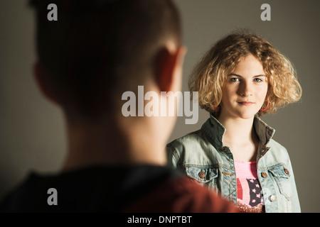Teenage Girl looking at Teenage Boy, Studio Shot - Stock Photo