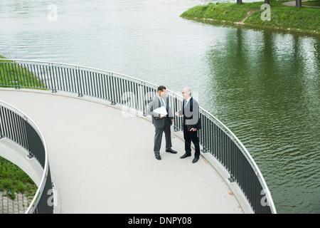 Mature businessmen standing on walkway talking, Mannheim, Germany - Stock Photo