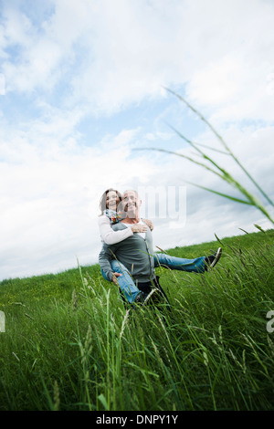 Mature couple in field of grass, man giving piggyback ride to woman, Germany - Stock Photo