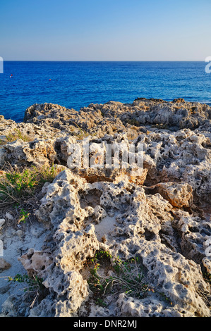 The setting sun shines on a rock formation at the Nissi Beach in Ayia Napa, Cyprus. - Stock Photo