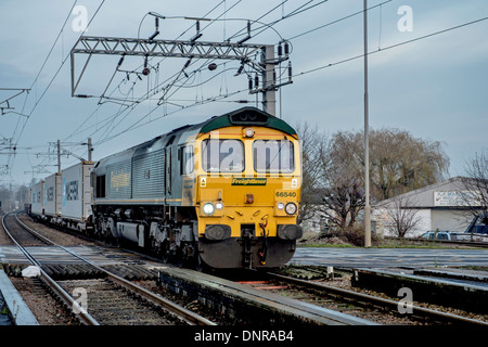 Goods Train passing over the level crossing. - Stock Photo