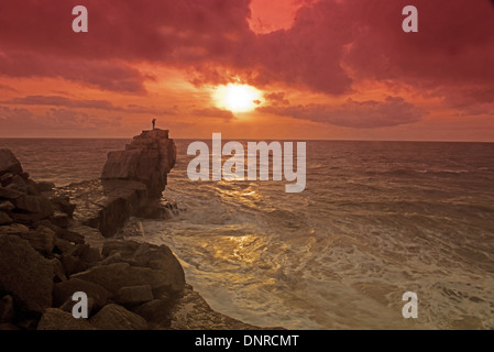 A Man Standing On top Of Pulpit Rock At Sunset, Isle of Portland, Portland Bill, Dorset, England.Uk - Stock Photo