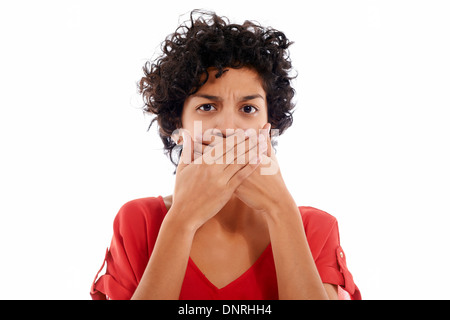 hispanic woman with hands covering mouth, speachless and angry, looking at camera - Stock Photo