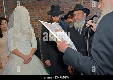 A orthodox religious Jewish bride and groom under a canopy at their wedding ceremony in Brooklyn, NY - Stock Photo