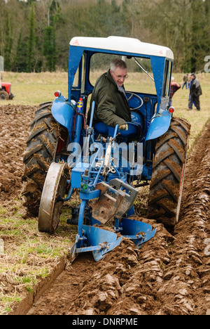 Farmer ploughing a field in a tractor - Stock Photo