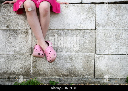 an 8 year old girls legs sitting on a whitewashed wall - Stock Photo