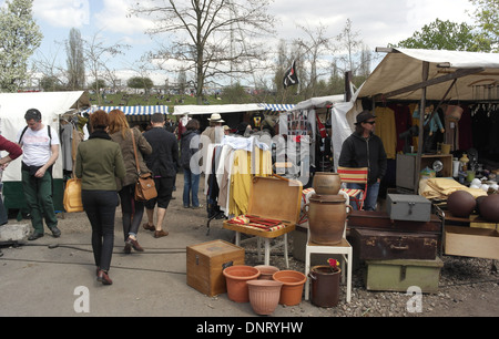 ... market day; Sunny view people walking concrete pathway by canopy stall with plant pots l&s vendor & Sunny view to canopy market stalls people walking three men ...