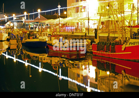 Trawlers at night reflecting on water Sutton Harbour Plymouth Barbican UK - Stock Photo