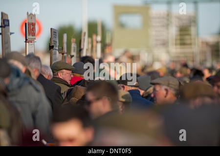 A bookie taking money from the crowd of people at the horse racing. - Stock Photo